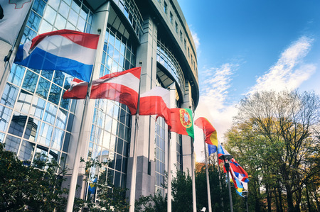 Waiving flags in front of European Parliament building at autumn day . Brussels, Belgium Stock Photo
