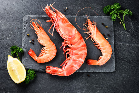 Fine selection of jumbo shrimps for dinner on stone plate. Food background Standard-Bild