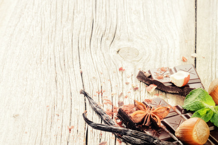 ground nuts: Dark chocolate tablet with vanilla and hazelnuts on old wooden background Stock Photo
