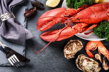 Fine selection of crustacean for dinner. Lobster, oysters and shrimps on dark background Foto de archivo