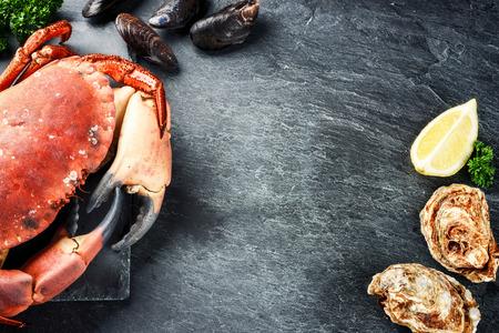 찐 게, 어두운 배경에 신선한 굴. 복사 공간 바다 음식 저녁 식사 개념 스톡 콘텐츠