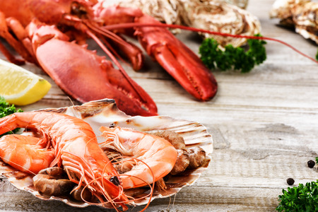 crustacean: Fine selection of crustacean for dinner. Lobster, jumbo shrimps and oysters on old wooden table