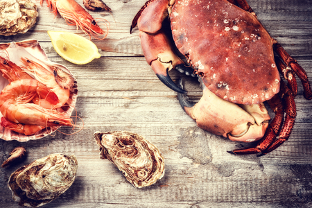 Steamed crab, shrimps and fresh oysters on wooden background. Sea food dinner concept Standard-Bild