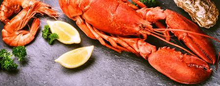 Fine selection of crustacean for dinner. Steamed lobster with lemon on dark background