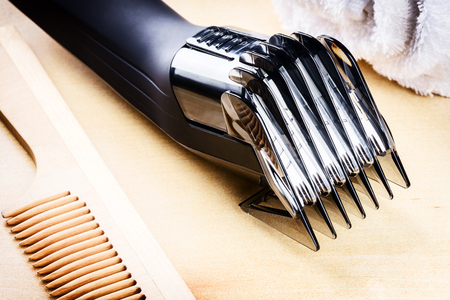hairclipper: Setting with hair clipper and wooden comb. Closeup shot