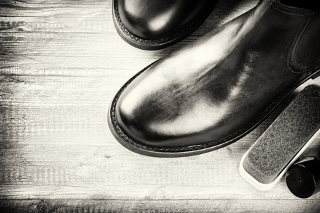 dubbing: Black boots and shoe care accessories on wooden background. Copy space