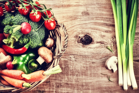green top: Fresh organic vegetables in basket. Healthy eating and cooking concept Stock Photo