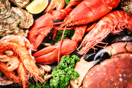 tiger shrimp: Fine selection of crustacean for dinner. Lobster, crab and jumbo shrimps and oysters on dark background