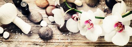 Spa-Einstellung mit weißen Orchideen, Kräuter-Massagekugel und ätherischen Ölen. Wellness-Konzept