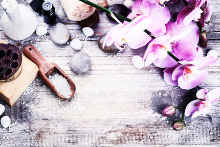 Spa setting with pink orchid, natural soap, herbal massage ball and essential oil. Wellness concept