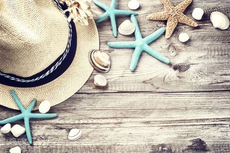 straws: Summer holiday setting with straw hat and seashells on wooden background
