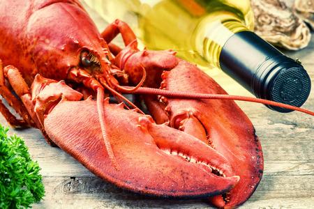 Fine sélection de crustacé pour le dîner. Étuvé homard avec une bouteille de vin blanc closeup
