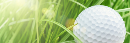 Golf ball over green grass background, closeup. Sport and leisure concept with copy space