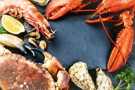 jumbo: Food frame with crustacean for dinner. Lobster, crab, jumbo shrimps and oysters on dark background Stock Photo