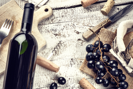 wine grape: Setting with bottle of red wine, grape and corks. Wine list concept