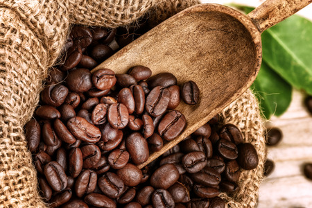 Roasted coffee beans in burlap sack with old wooden scoop. Closeup Stock Photo