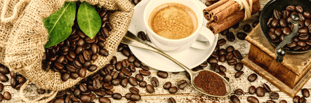 Cup of hot black coffee in retro setting with old wooden mill grinder and burlap sack with roasted coffee beans. Copy space Banque d'images
