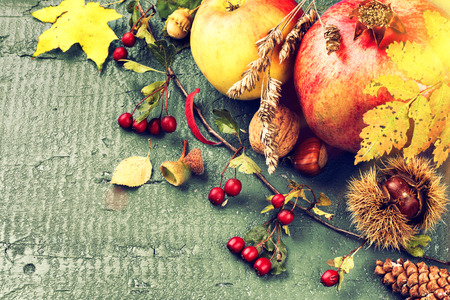 grunge backgrounds: Autumn still life with pomegranate, apple and fall leaves over blue wooden background. Fall background with copy space