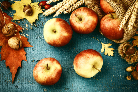 Autumn still life with fresh apples and fall leaves over blue wooden background. Fall background