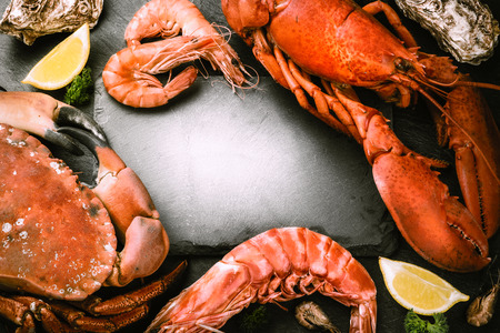 Food frame with crustacean for dinner. Lobster, crab, jumbo shrimps and oysters on dark background with copyspace Standard-Bild