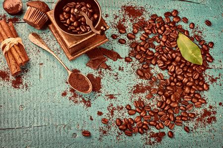 Marco de café con granos de café tostado, palitos de canela, antiguo molino de molino de madera y chocolate. Copiar espacio