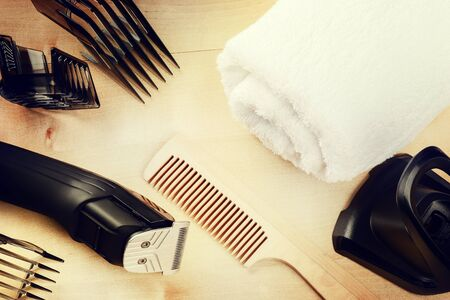 hairclipper: Setting with hair clipper and wooden comb. Beauty and haircare background with copyspace Stock Photo