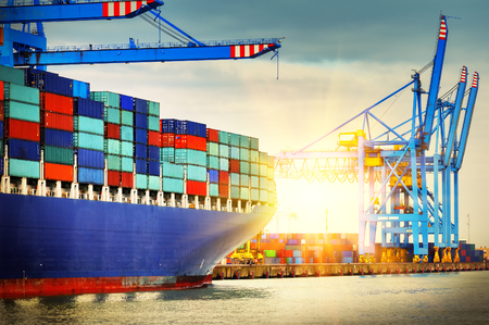 industry: Container ship with full of cargo entering a port at sunset. Transportation background