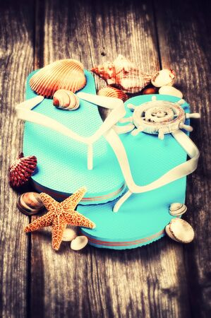 old items: Summer holiday setting with flip flops and sea shells on old wood background