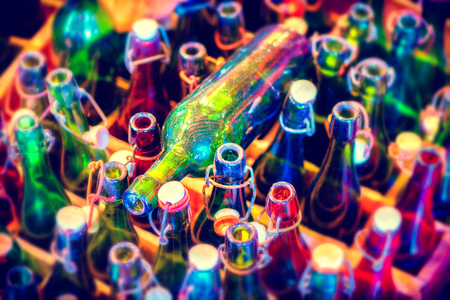 Multicolor background with empty beer bottles, top view. Food and drink concept