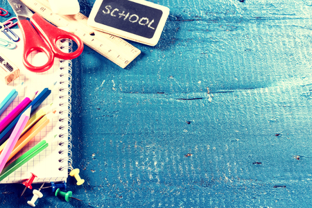 vintage background: Colorful school supplies over blue background with copyspace. Back to school concept