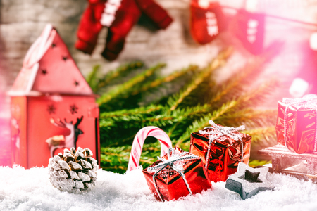 Christmas holiday setting with Santa clothes garland, red presents laying in snow. Christmas background in red and green tone Stockfoto