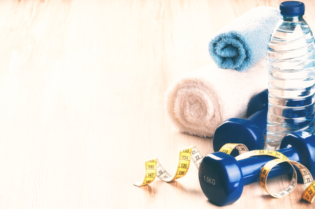 Fitness concept with dumbbells, cotton towels and water bottle. Health and sport background