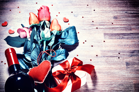 St Valentines setting with multicolor roses bouquet, present and red wine bottle. Greeting card with copy space