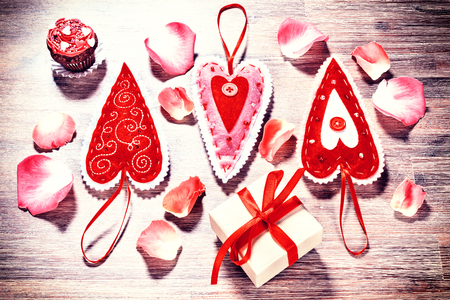 Valentines day background with decorative hearts and rose petals on wood background. Love and romance concept