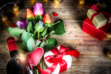 Bouquet of multicolor roses with decorative heart and presents. St Valentines concept with copy space