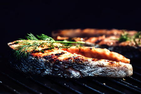 Salmon steaks cooking on barbecue grill for summer outdoor party. Food background with barbecue party