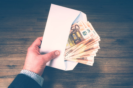 Man holding pile of 50 euro banknotes in white envelope. Finances and budget concept