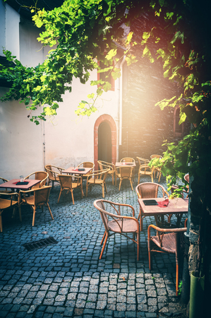 Cafe terrace in small European city at sunny summer day. Food industry
