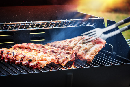 Spare ribs cooking on barbecue grill for summer outdoor party. Food background with barbecue party