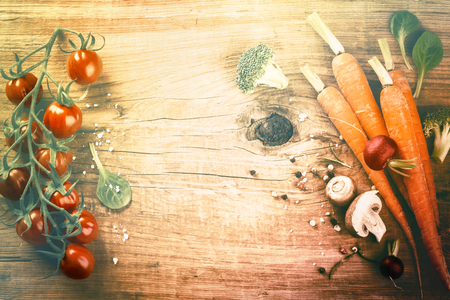 Cooking setting with fresh organic vegetables on old wood background. Healthy eating concept with copy space
