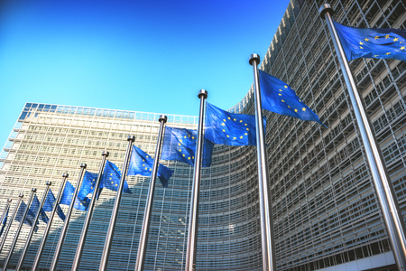 Waving EU flags in front of European Commission in Brussels