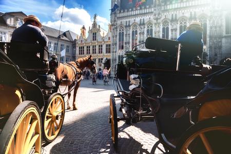 Horse-drawn carriages waiting for tourist tour. Bruges, Belgium Banco de Imagens