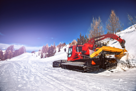 Winter landscape with snow plowing bulldozer. Snow removal equipment for a ski resort. Mountains background 免版税图像