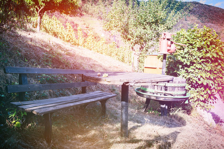 Landscape with autumn vineyards and picnic place next to vintage wine press. Nature background