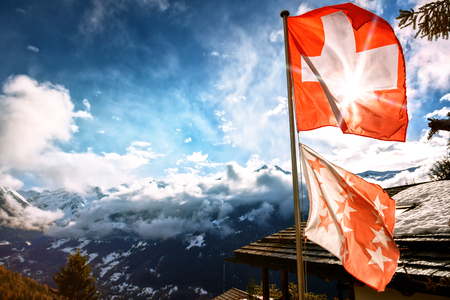 Winter landscape with mountain peaks and Swiss flag. Nature background Stok Fotoğraf