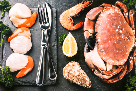 Fine selection of crustacean for dinner. Crab, scallops and oysters with cutlery over dark background Stock Photo
