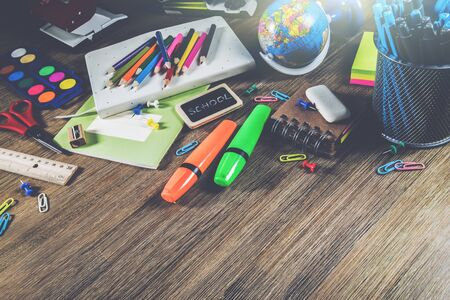Colorful school supplies over wooden desktop. Back to school concept
