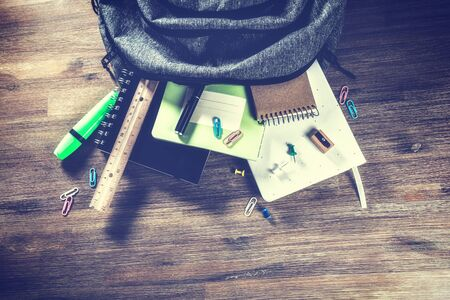 Backpack with school supplies, top view. Back to school concept with copy space