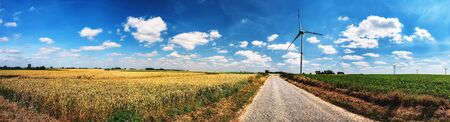 Panoramic summer landscape with country road and wind turbines. Ecology background Stok Fotoğraf