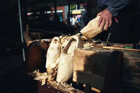 Making of traditional wooden Dutch shoes - clogs at local market Stock Photo
